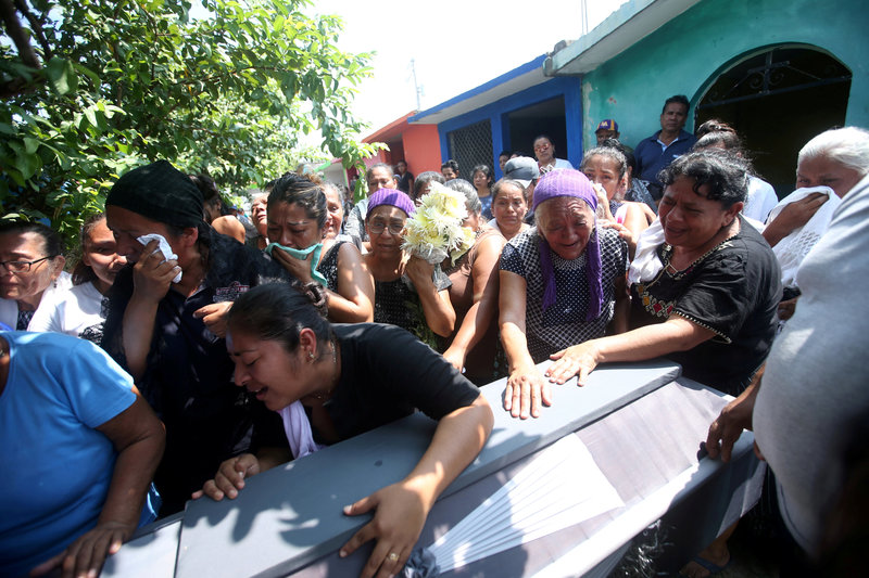 People participate in the burial of a victim of the earthquake that struck in Juchitan