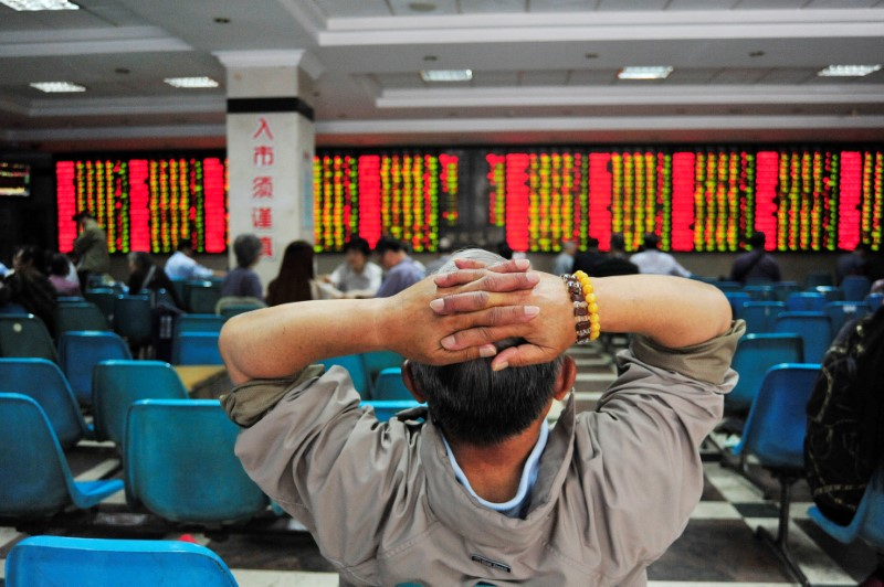 Investor looks at electronic board showing stock information at brokerage house in Nanjing