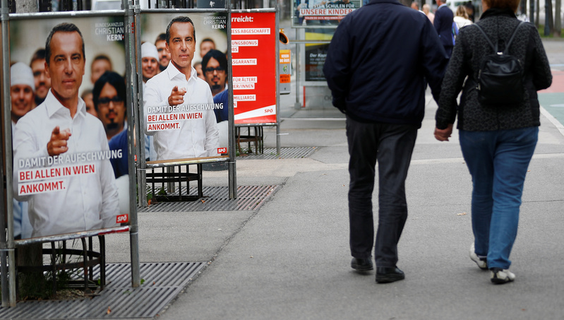 People walk past election campaign posters of Social Democrats in Vienna
