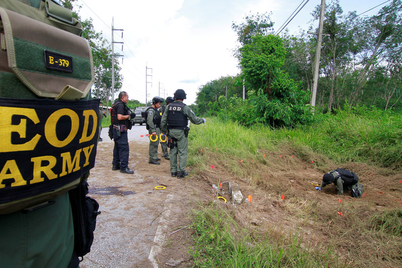 Military personnel check the place where a roadside bomb blast occurred in the southern province Malay Muslim province of Yala
