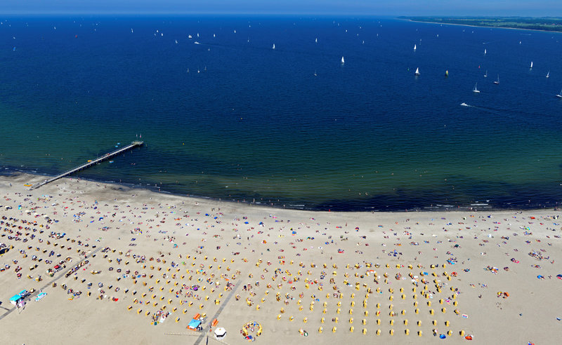 FILE PHOTO: People sunbathe at a beach in Travemuende at the Baltic Sea