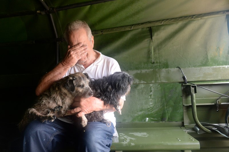 An evacuee holding two dogs reacts after his rescue by Texas National Guardsmen from severe flooding due to Hurricane Harvey in Cypress Creek