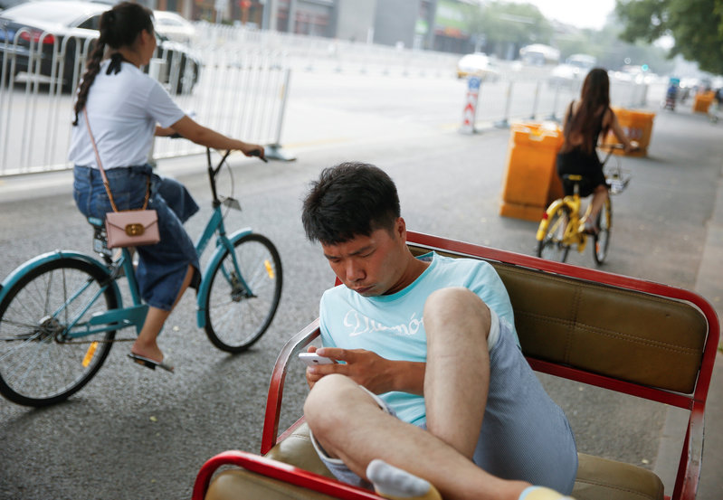 FILE PHOTO: A electric rickshaw driver uses a mobile phone as he takes a break in Beijing