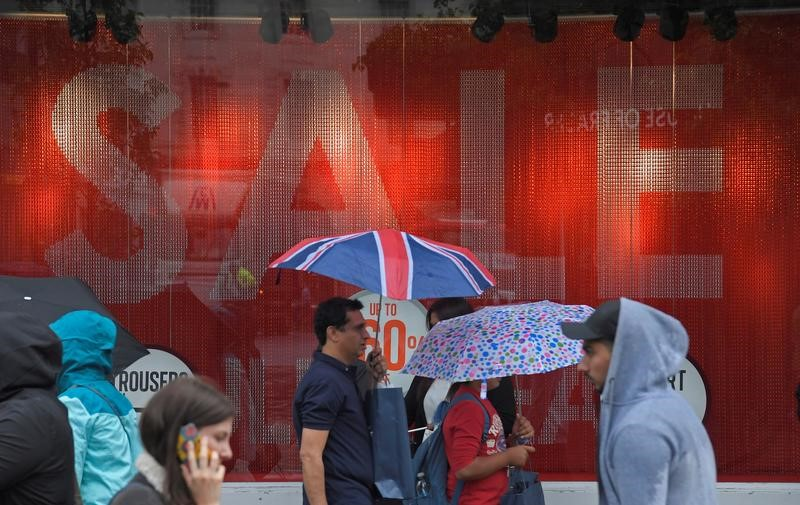 FILE PHOTO: Shoppers walk past a sale sign in central London