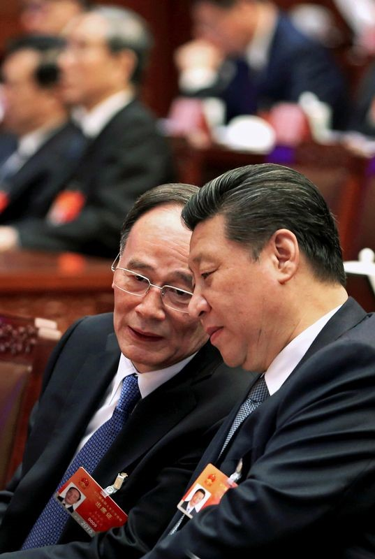 China's President Xi Jinping speaks to Wang Qishan, the head of China's anti-corruption watchdog in Beijing