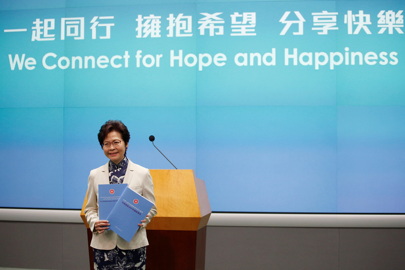 Hong Kong Chief Executive Carrie Lam poses with copies of her policy speech in Hong Kong