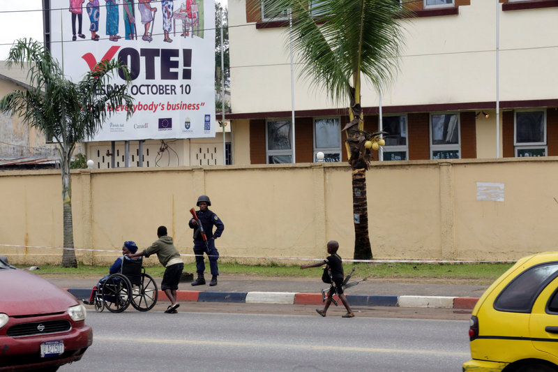 A anti-Riot police officer stands guard at National Election Commission headquarters in Monrovia