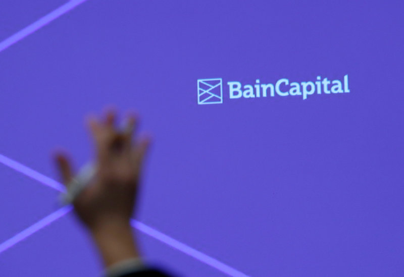 FILE PHOTO: A reporter raises his hand to ask a question during a news conference by Bain Capital LP Managing Director Sugimoto in Tokyo