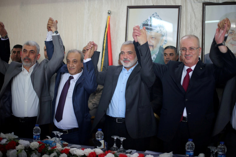 FILE PHOTO: Palestinian Prime Minister Rami Hamdallah and Hamas Chief Ismail Haniyeh hold hands in Gaza City