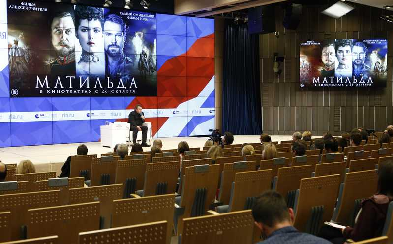 Participants listen to Russian film director Uchitel during a news conference in Moscow