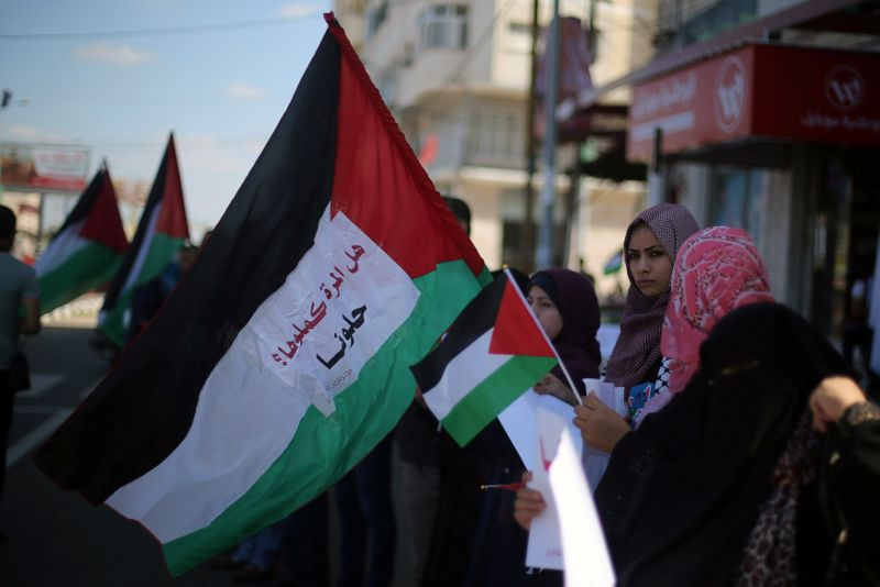 Women hold Palestinian flags as they celebrate after rival Palestinian factions Hamas and Fatah signed a reconciliation deal, in the central Gaza Strip