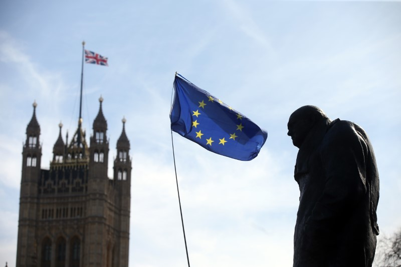 An EU flag flies between the statue of Winston Churchill and a Union Flag flying from the Big Ben clock tower, during a Unite for Europe rally in Parliament Square, in central London