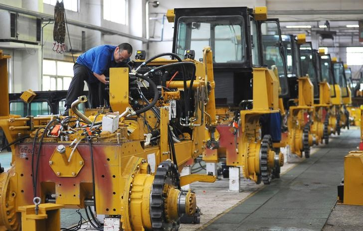 An employee works at an assembly line of bulldozers at a factory in Zhangjiakou