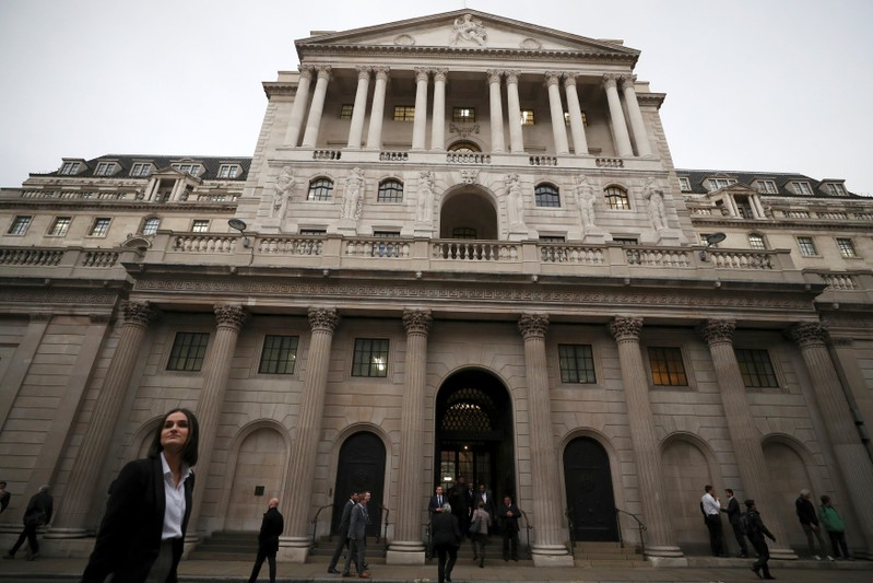 People walk past the Bank of England in London