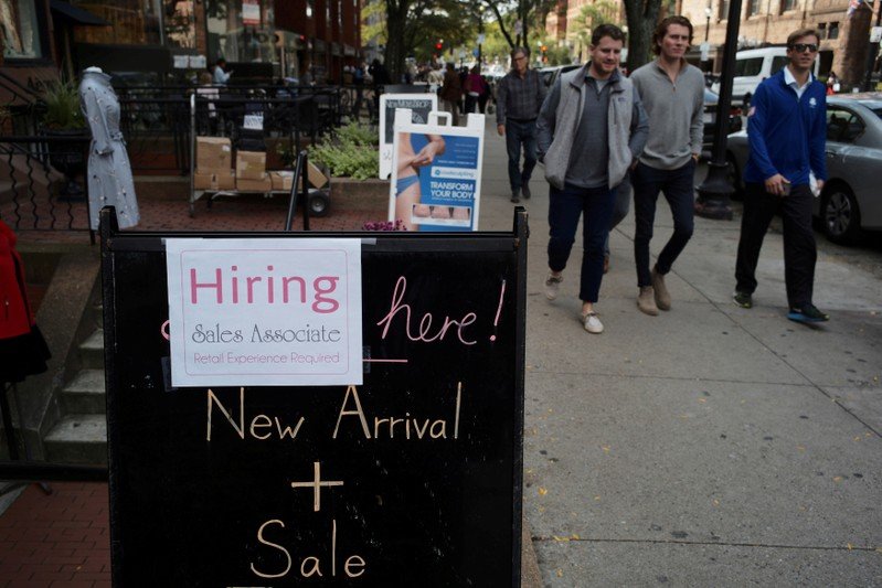 FILE PHOTO: Pedestrians pass a sign advertising a sale and a job opening at a shop on Newbury Street in Boston