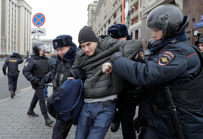 Police officers detain a man suspected of being anti-government protester in the centre of Moscow