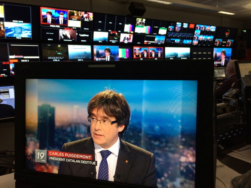 Ousted Catalan President Carles Puigdemont appears appears on a monitor during a live TV interview on a screen in a bar in Brussels