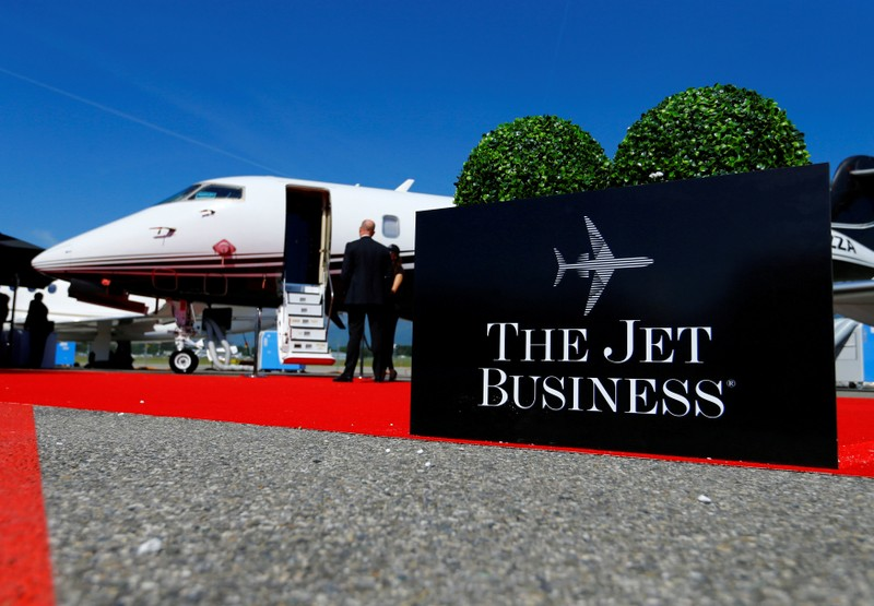 FILE PHOTO: Visitors stand next to an aircraft at the The Jet Business booth during EBACE in Geneva