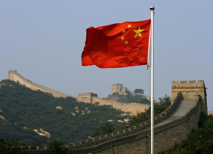 A Chinese flag flies in front of the Great Wall of China, located north of Beijing