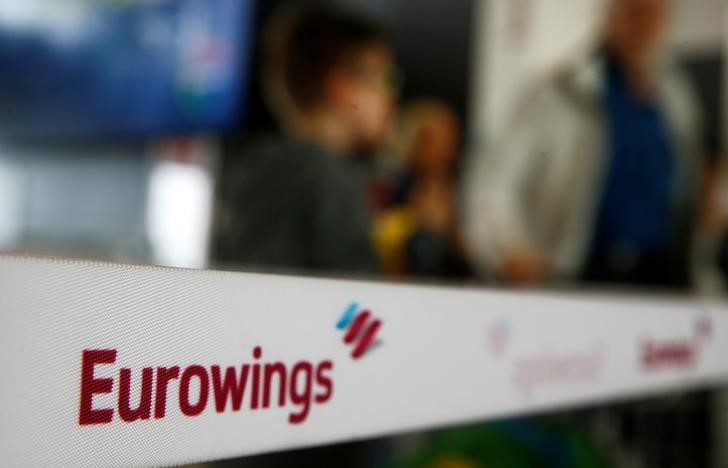 People line up behind a barrier tape of Lufthansa's budget airlines Eurowings during a 24-hour strike over pay and working conditions at Cologne-Bonn airport