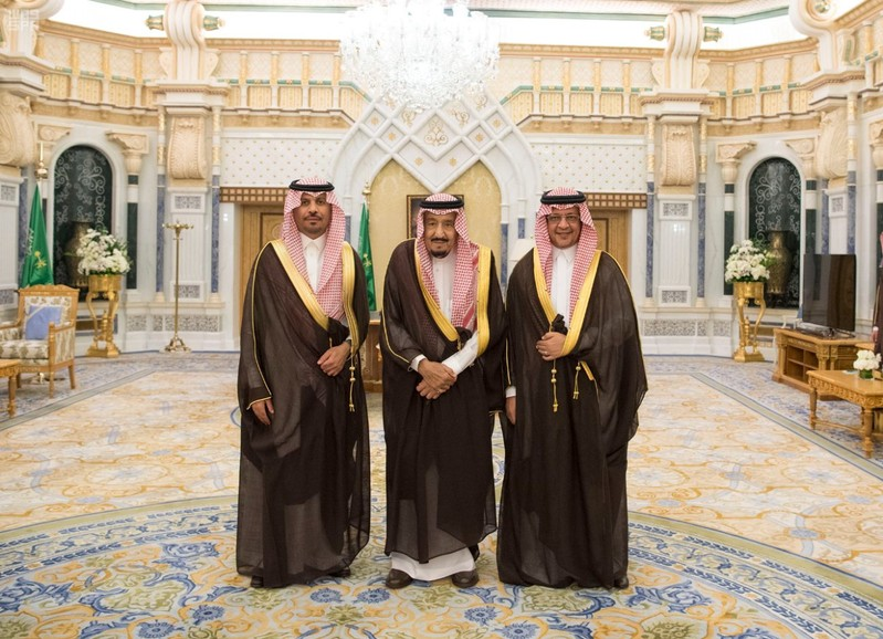 Saudi King Salman bin Abdulaziz Al Saud poses for a photo with National Guard Minister Khaled bin Ayyaf and Economy Minister Mohammed al-Tuwaijri during a swearing-in ceremony in Riyadh