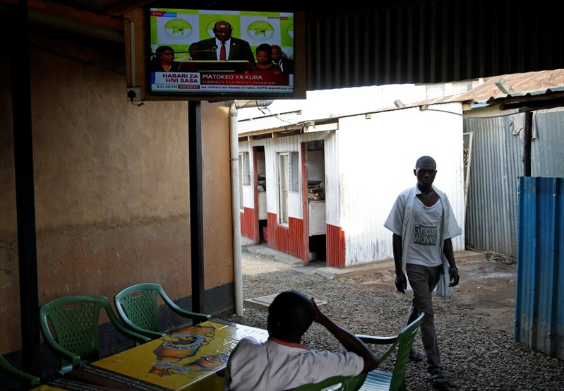 People watch on television the announcement of the winner of polls in Kenya's repeat presidential election in Kisumu
