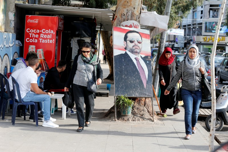 People walk next to a poster depicting Lebanon's Prime Minister Saad al-Hariri, who has resigned from his post, along a street in the mainly Sunni Beirut neighbourhood of Tariq al-Jadideh in Beirut