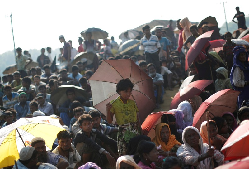 Rohingya refugees sit as they wait to receive humanitarian aid at Balu Khali refugee camp