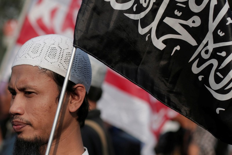 A man holds a Hizbut Tahrir Indonesia flag during a protest against the President Joko Widodo's decree to disband Islamist groups in Jakarta
