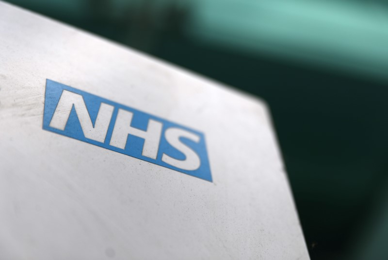 An NHS logo is displayed outside a hospital in London