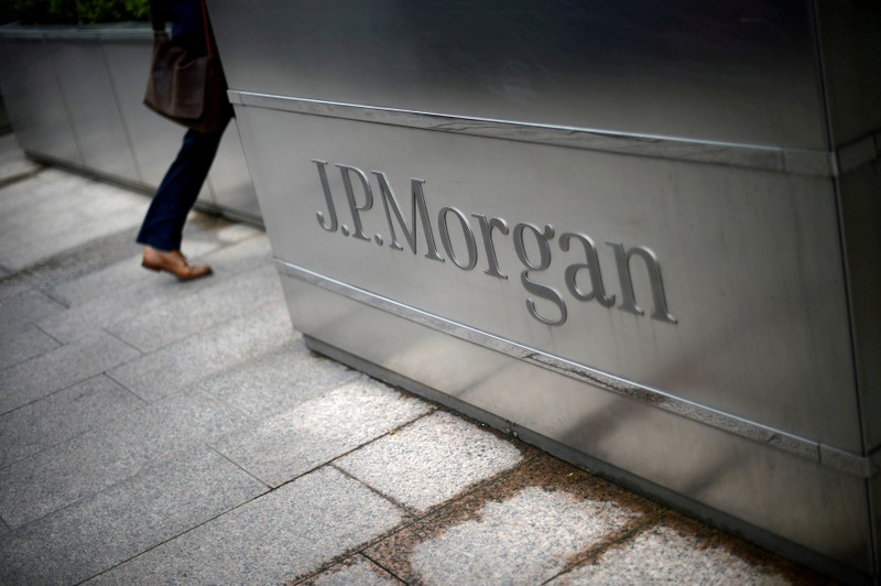 FILE PHOTO: A man walks into the JP Morgan headquarters at Canary Wharf in London