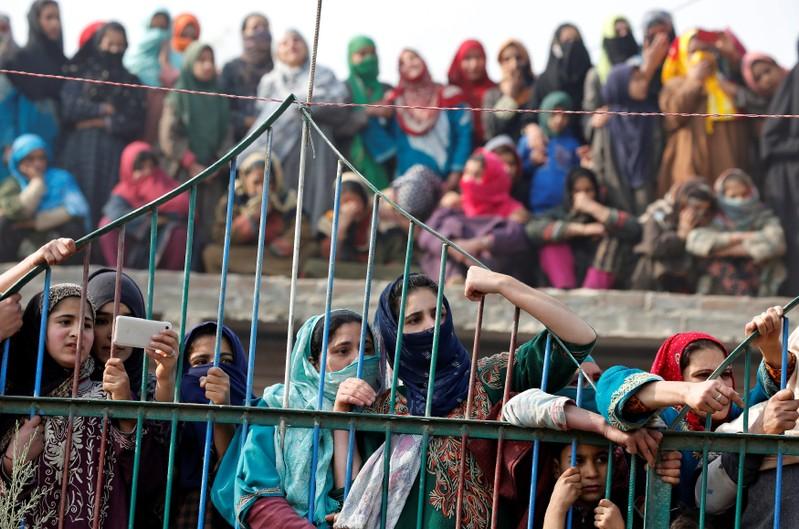 Girls watch the body of Waseem Ahmad, a suspected militant who according to local media was killed on Monday evening in a gunbattle with Indian security forces, being carried away during his funeral in Drubgam