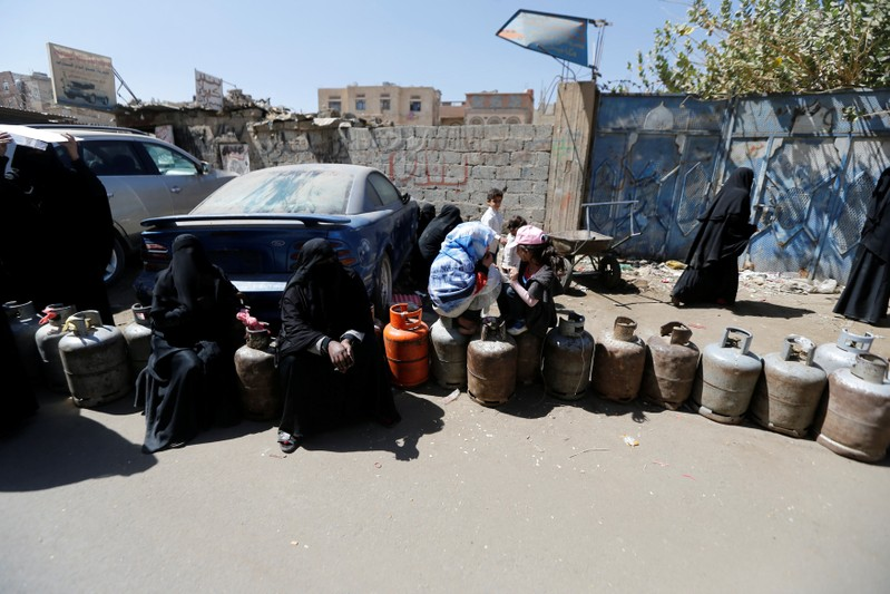 Women sit on cooking gas cylinders lined up outside a gas station amid supply shortage in Sanaa