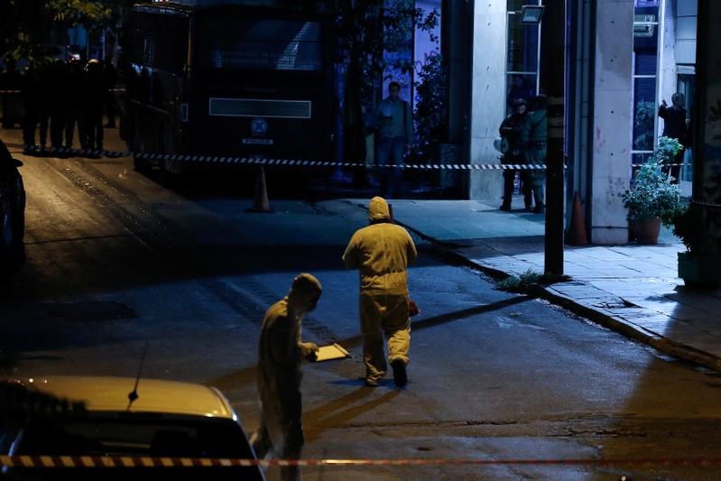 Police investigators search for evidence following a gun attack outside the headquarters of Greece's socialist Pasok party in central Athens