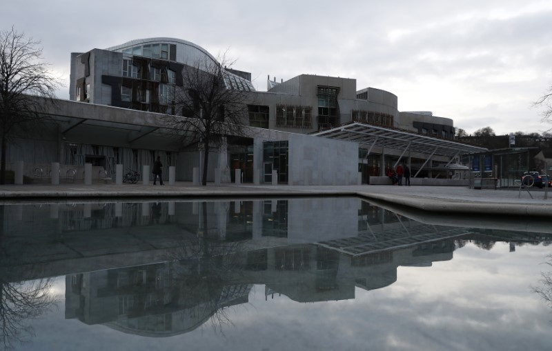 The Scottish Parliament is reflected in a pond in Holyrood Edinburgh, Scotland