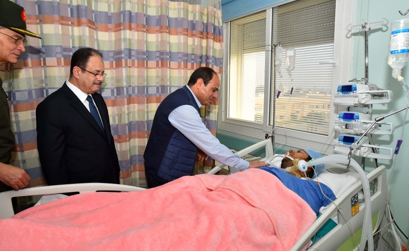 Egyptian President Abdel Fattah al-Sisi visits police officer Mohamed El-Hayes who was rescued after being kidnapped during an attack in the Western Desert, at a military hospital in Cairo