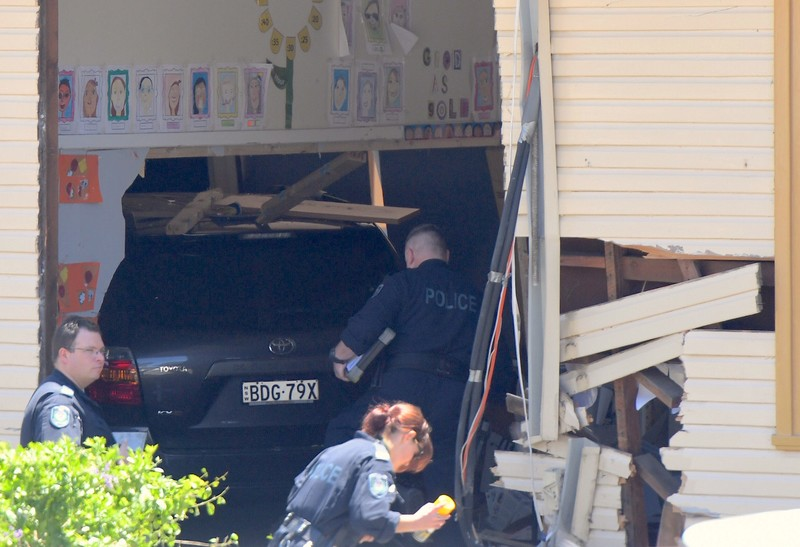 New South Wales emergency services personnel and police inspect a vehicle that crashed into a primary school classroom in the Sydney suburb of Greenacre