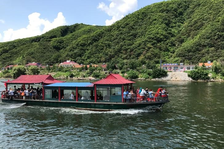Chinese tourists are seen a boat taking them from the Chinese side of the Yalu River for sightseeing close to the shores of North Korea, near Dandong