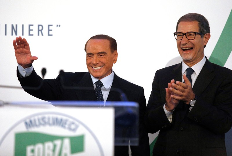 Forza Italia party leader Silvio Berlusconi waves to supporters next to local candidate Nello Musumeci during a rally in Catania