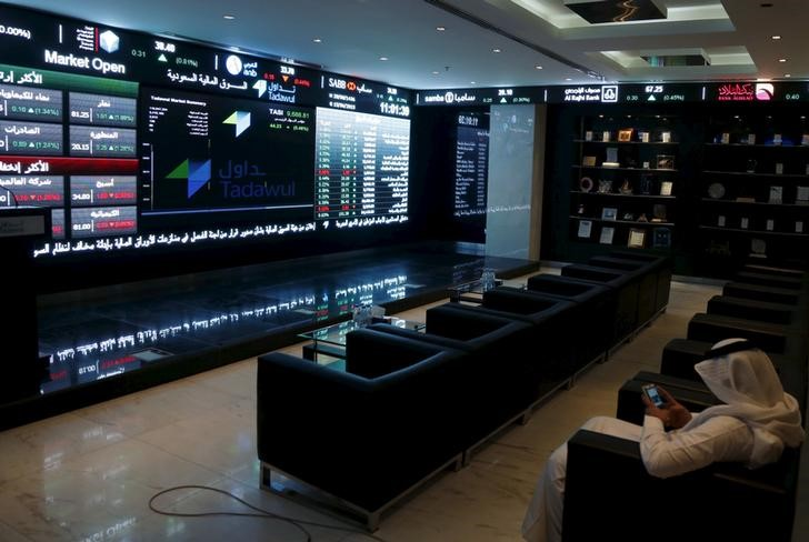 FILE PHOTO - A trader uses his mobile as he monitors screens displaying stock information at the Saudi Stock Exchange (Tadawul) in Riyadh