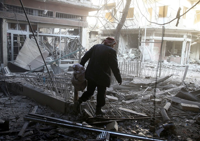 A man walks on rubble after an airstrike in the rebel-held city of Douma