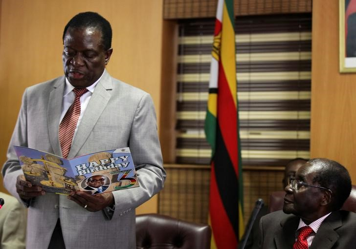 Zimbabwe's President Robert Mugabe looks on as his deputy Emmerson Mnangagwa reads a card during Mugabe's 93rd birthday celebrations in Harare