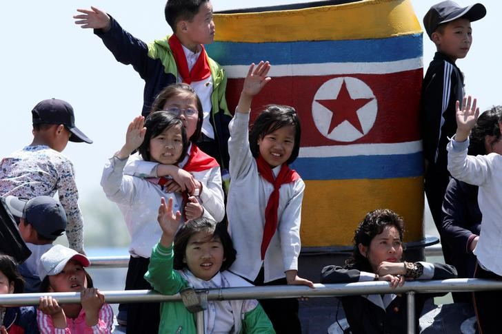 North Korean children wave during their tour on the Yalu River in Sinuiju, near the Chinese border city of Dandong