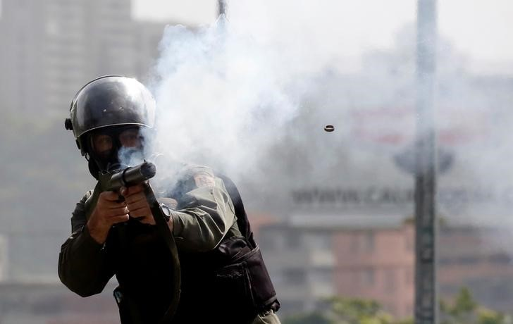 A member of the security forces fires his gun during clashes at a protest against Venezuelan President Maduro's government in Caracas