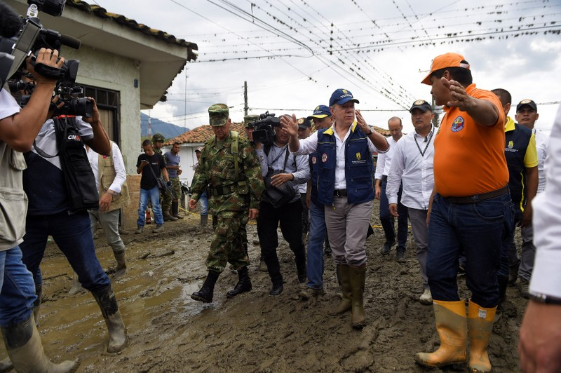 Colombia's President Juan Manuel Santos walks down a street after floods and landslides, caused by heavy rains where a river overflowed, pushed sediments and rocks into houses and roads, in Corinto