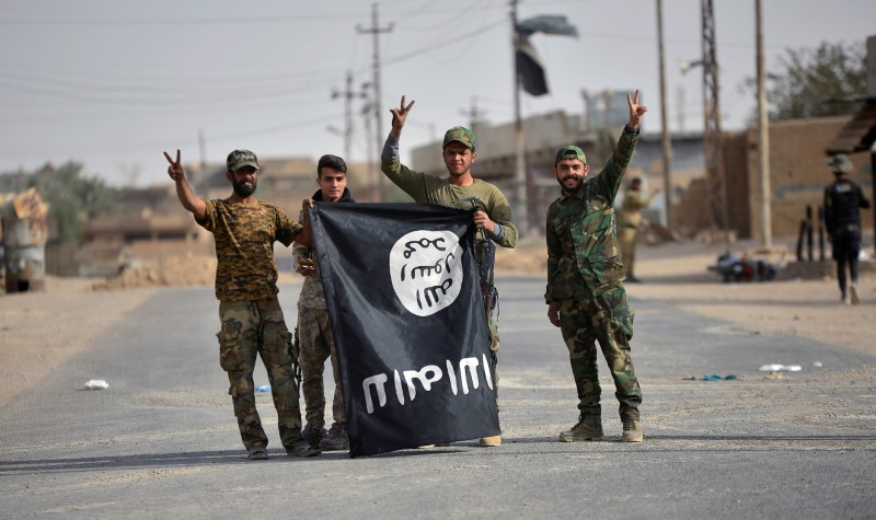 Shi'ite Popular Mobilization Forces (PMF) fighters carry the Islamic State militants flag downward after liberating the city of Al-Qaim
