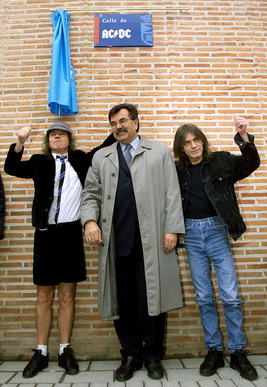 Angus and Malcolm Young, founder members of AC/DC, flank Jose Luis Perez, mayor of the Madrid district of Leganes, following the inauguration of a new street with the group's name, in Leganes