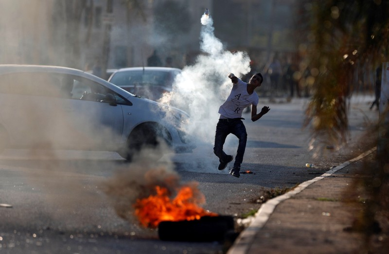 A Palestinian protester hurls back a tear gas canister fired by Israeli troops during clashes in the West Bank village of Qusrah near Nablus