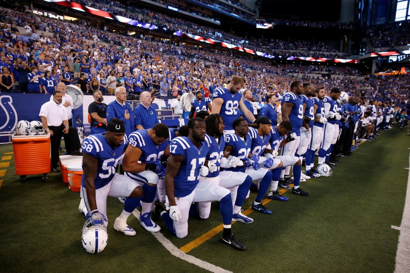 FILE PHOTO: Indianapolis Colts players kneel during the playing of the National Anthem before the game against the Cleveland Browns at Lucas Oil Stadium in Indianapolis