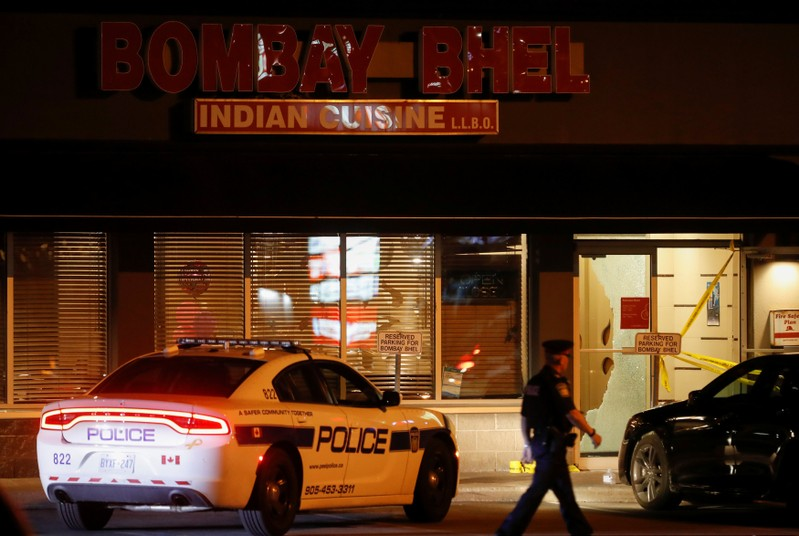Police officer walks in front of Bombay Bhel restaurant, where two unidentified men set off a bomb, in Mississauga